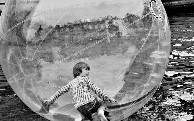 Junge in einem durchsichtigem Ball auf einem Fluss