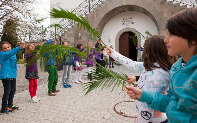 Untikinder stehen Spalier vor der Kirche, Palmsonntag